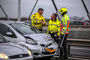 Police officers from the Road Traffic Accident Analysis Department (VOA) and a Rijkswaterstaat roads inspector at an accident on the Van Brienenoord Bridge (photograph: AS Media)
