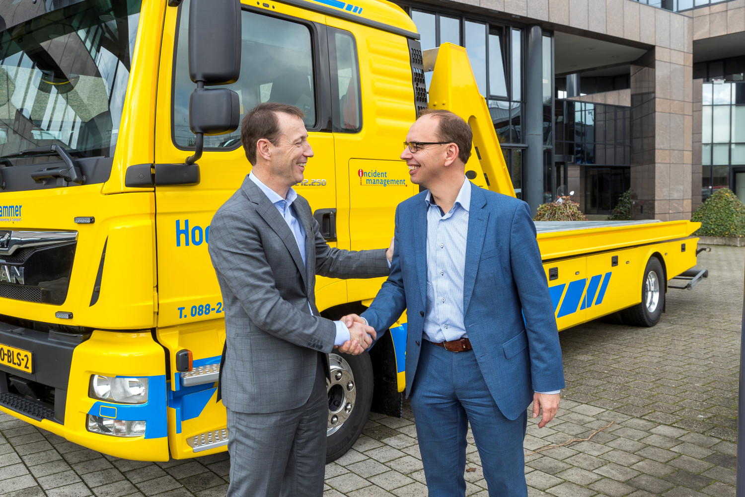Ryan Florijn (R), chair of Stichting IMN, congratulates Hans Coffeng, managing director of CED, on the transfer of the LCM, in front of the offices of SOS International in Amsterdam-Zuidoost on 5 November 2019.